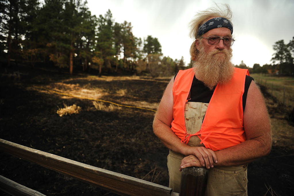 . BLACK FOREST, CO - JUNE 17:   Mike Turner is seen along the fence line of his mother\'s property along Shoup Road inside the Black Forest Burn area on June 17, 2013.  His mother, who is 90 years old, has lived in the Black Forest for 49 years.  She lost everything in the fire.  This is her property that Turner is standing on. Turner never evacuated and stayed with a friend across the street and tried to save what he could during the firestorm.  Photo by Helen H. Richardson/The Denver Post)