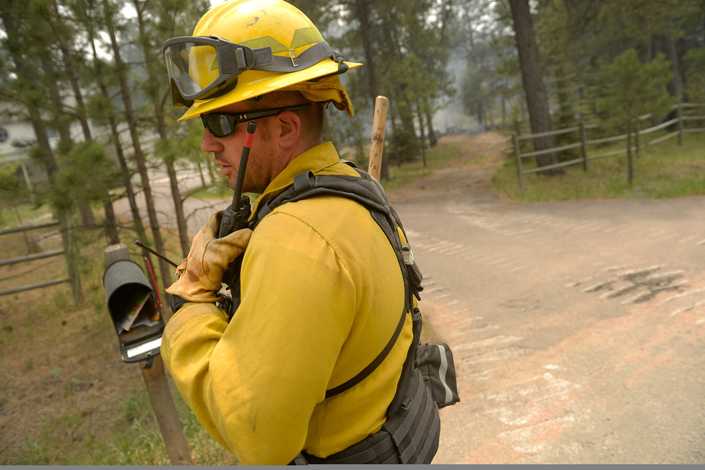 . Ryan Hawley, with the National Guard out of Fort Carson, directs his firefighters to a house to help put out small fires in and around structures near Winchester Road north of  Hodgen Road in the midst of the Black Forest Fire on June 13, 2013.  Photo by Helen H. Richardson/The Denver Post)