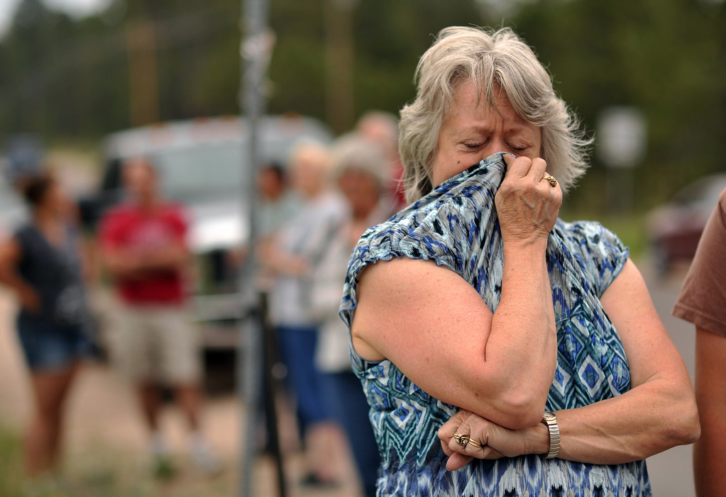 . Black Forest Fire evacuee Karen Hilborn covers her face from smoke during her waiting El Paso County Sheriff\'s escort to their property at the corner of Vollmer Rd. and Burgess Rd., June 14, 2013. Firefighters continue to battle the Black Forest fire north of Colorado Springs that has consumed 15,700 acres and 379 homes. (Photo By Hyoung Chang/The Denver Post)