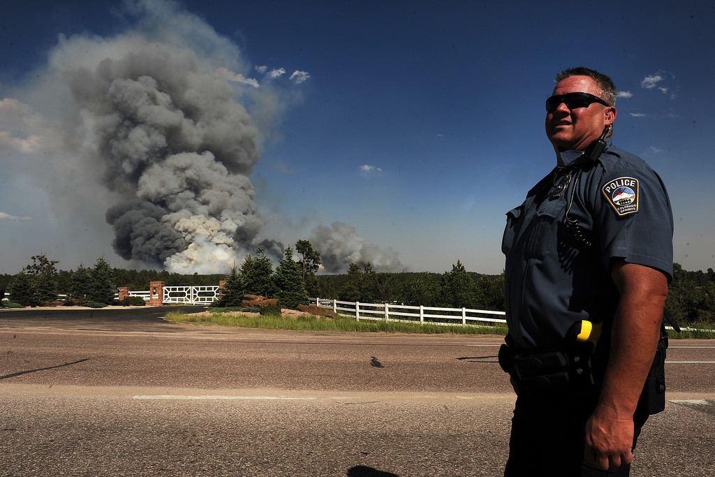. COLORADO SPRINGS, CO - JUNE 11: Colorado Springs patrolman Herb Tomitsch watches as a huge plume of smoke continues to grow along Highway 83 near Colorado Springs, CO on June 11, 2013.  A wild land fire started around 2:00 in the Black Forest northeast of Colorado Springs, CO on June 11, 2013.  Homes have already burned and the wind is expected to continue through the afternoon.  Photo by Helen H. Richardson/The Denver Post)