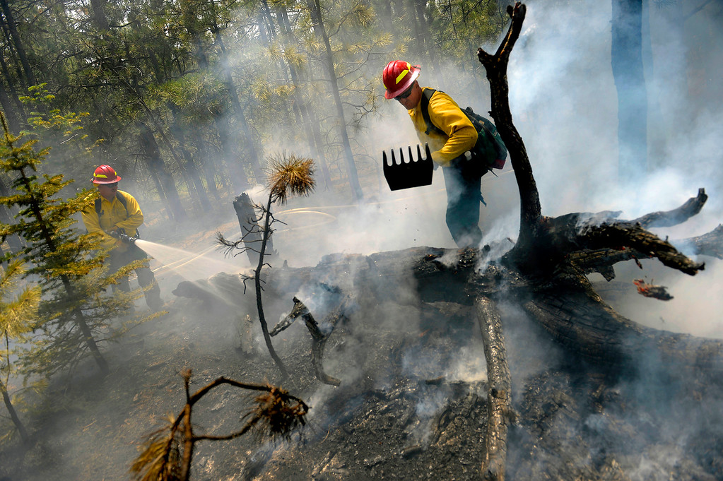 . Sgt. 1st Class John Screiber, right, and Sgt. David Meggison extinguish a burning tree on property along Winchester Road north of Hodgen Road in the middle of the Black Forest fire on June 13, 2013. They are members of a firefighting crew with the National Guard from Fort Carson. The crew used a water tender that carries 2,500 gallons of water to fight fire in an area that has no fire hydrants.