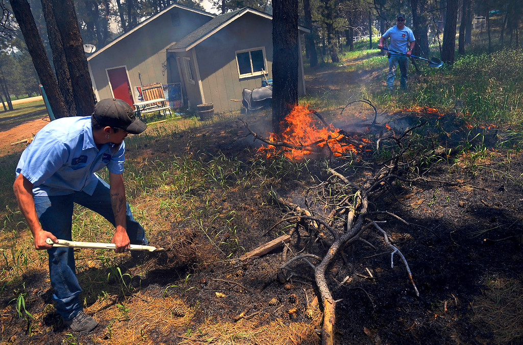 . Matt Newland, left, and his friend Chad Mazari use shovels to put out small spot fires near a neighbor\'s home off Cyprus Road in the Black Forest on June 12, 2013. Both men, who ignored evacuation orders, had packed their belongings and had an escape route in mind in case they needed to leave quickly.