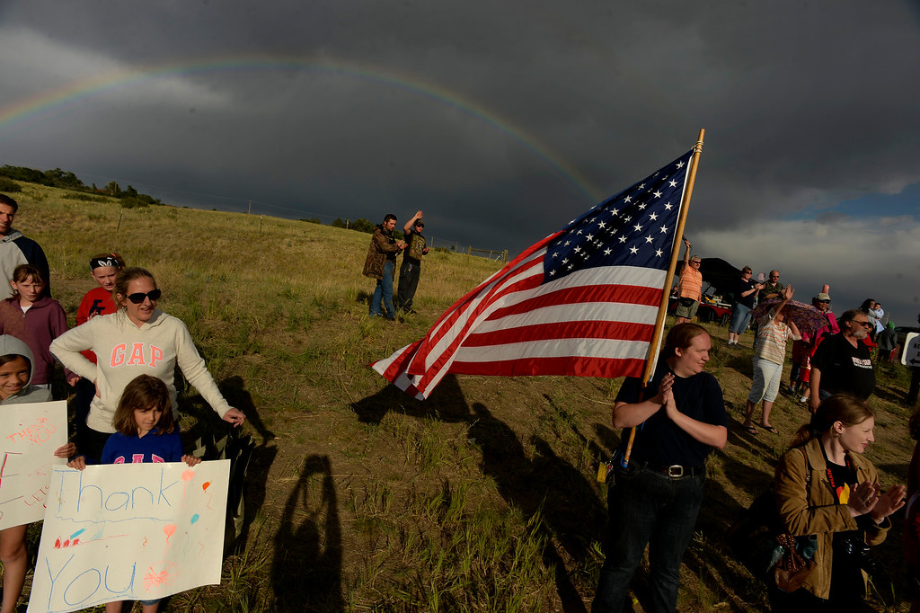 . BLACK FOREST, CO - JUNE 17:   Cyrena McVey holds up a large American flag while a beautiful double rainbow sits over the Black Forest Fire burn area while Colorado Springs residents turn out each and every night with signs and flags to cheer on the firefighters as they come off the line for the night from fighting the Black Forest Fire in Black Forest on June 17, 2013.  Photo by Helen H. Richardson/The Denver Post)