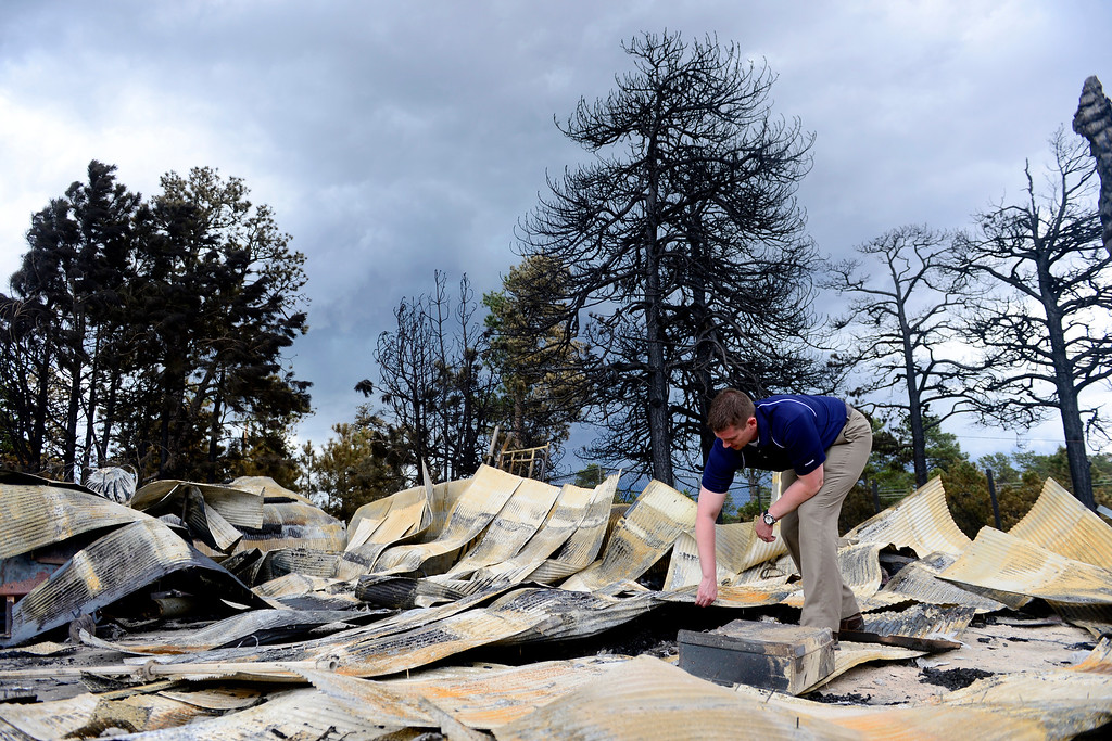 . COLORADO SPRINGS, CO - JUNE 18: Jesse Russow surveys the damage of his rental property, which was the southernmost home burned on the west side of Vollmer Road. The occupant of the home, who was not named, was only able to save himself and his motorcycle as he was away from the property when the evacuation took place. Russow is accepting donations for fire crews at 7195 Templeton Gap Road in Colorado Springs. (Photo by AAron Ontiveroz/The Denver Post)