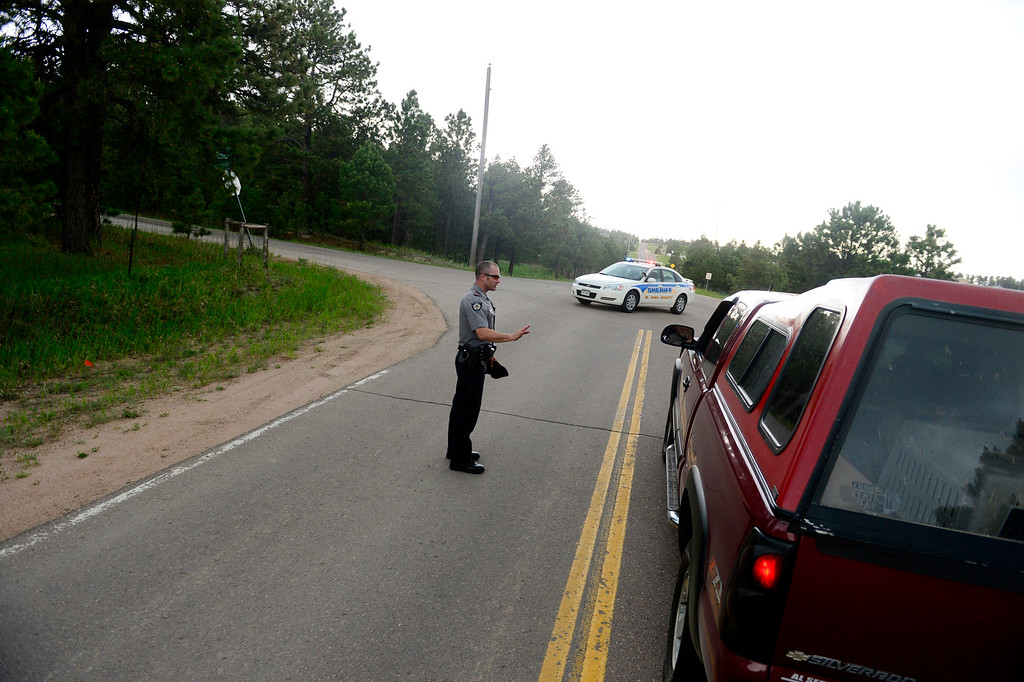 . COLORADO SPRINGS, CO - JUNE 17: Andrew Thompson, of the El Paso County Sheriff\'s department, checks the IDs of residents before letting them cross a roadblock at the intersection of Wildridge and Herring Roads. As of Sunday, some select area evacuated Black Forest fire residents were allowed to return to their homes. (Photo by AAron Ontiveroz/The Denver Post)