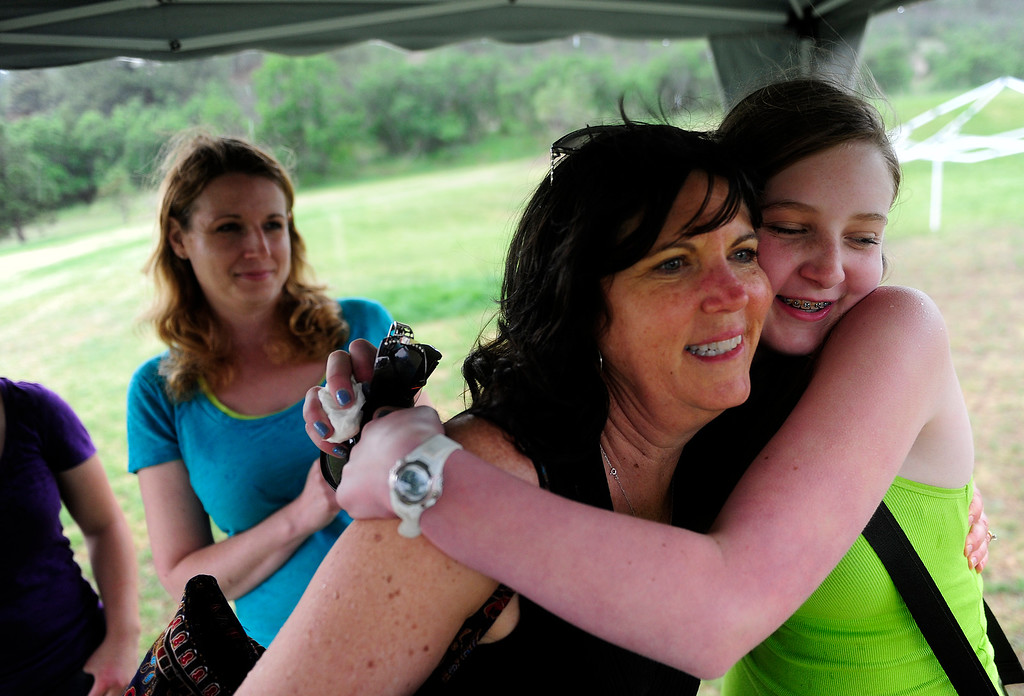 . COLORADO SPRINGS - JUNE 17: Caitlyn DelMonico, right, hugs Suzanne Lung, as her mother Delcine DelMonico watches, at the end of a picnic Waldo Canyon evacuees and community members put on to support those affected by the Black Forest Fire on Monday, June 17, 2013. Lung and Wendy Reis, not pictured, got the idea to put on the picnic after seeing the DelMonico\'s on TV after they lost their home.(Photo By Grant Hindsley / The Denver Post)