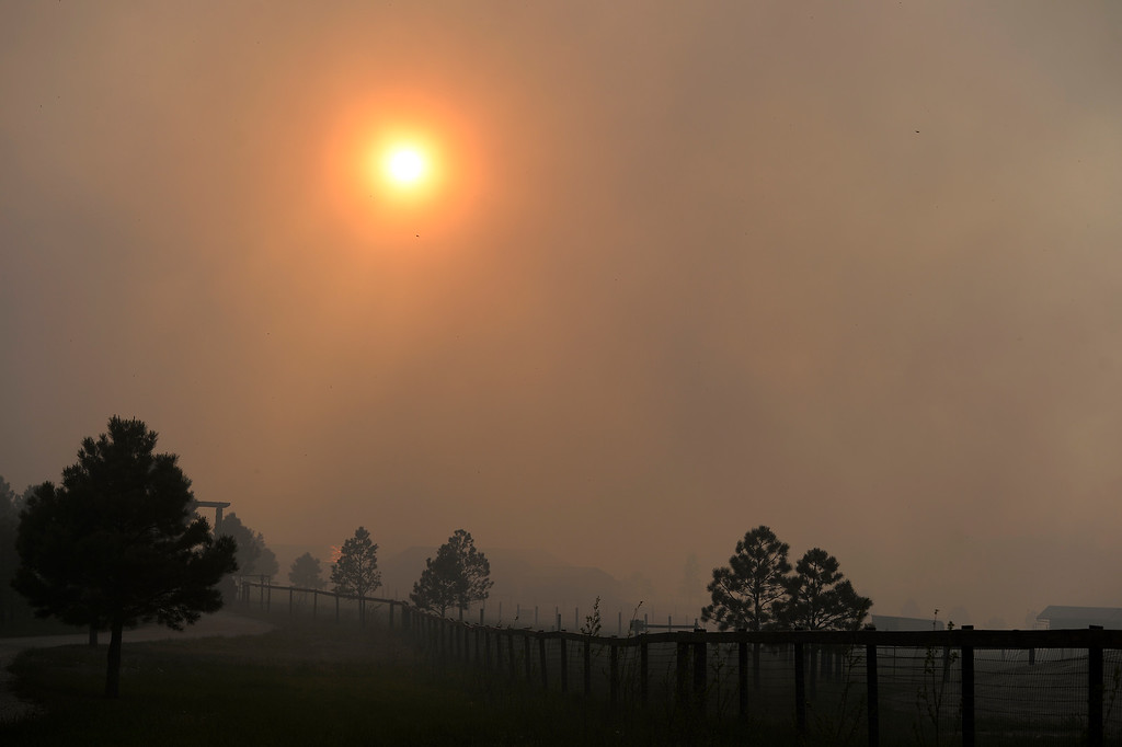 . COLORADO SPRINGS, CO - JUNE 11: Smoke filled sky obscures the sun as the Black Forest Fire advances towards Herring Road in the Black Forest northeast of Colorado Springs, CO on June 11, 2013. Many homes have already been lost to the raging fire that continues to burn out of control. Photo by Helen H. Richardson/The Denver Post)