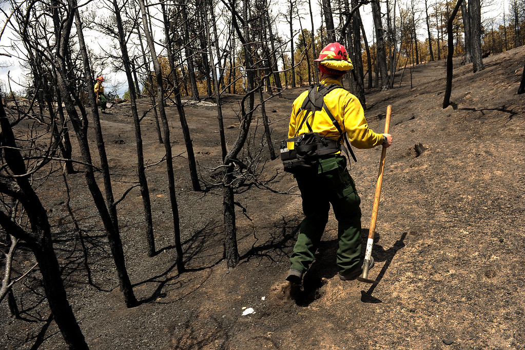 . BLACK FOREST, CO - JUNE 17:   Aaron Cariato, a firefighter with Salida Fire and Rescue, checks for any kind of hotspots in houses inside the Black Forest fire zone on June 16, 2013. Officials want to make sure that all hotspots are out completely. The crew also looks above in the burned canopy of trees looking for any limbs or trees that might fall over that might injure someone.  The fire is now 75% contained and recent rains are helping firefighters. Photo by Helen H. Richardson/The Denver Post)