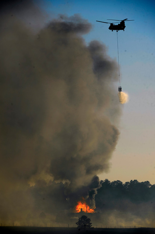 . COLORADO SPRINGS, CO - JUNE 11: A Blackhawk helicopter makes a water drop on a burning structure in the midst of the Black Forest Fire in Colorado Springs, CO on June 11, 2013.. Many homes have already been lost to the raging fire that continues to burn out of control. Photo by Helen H. Richardson/The Denver Post)