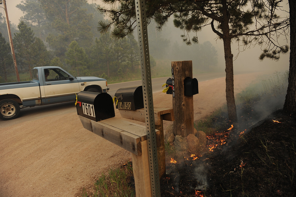 . COLORADO SPRINGS, CO - JUNE 11: A man braves the smoke and heads into the fire in his pick up truck on Herring Road in the midst of the Black Forest Fire in Colorado Springs, CO on June 11, 2013.. Many homes have already been lost to the raging fire that continues to burn out of control. Photo by Helen H. Richardson/The Denver Post)
