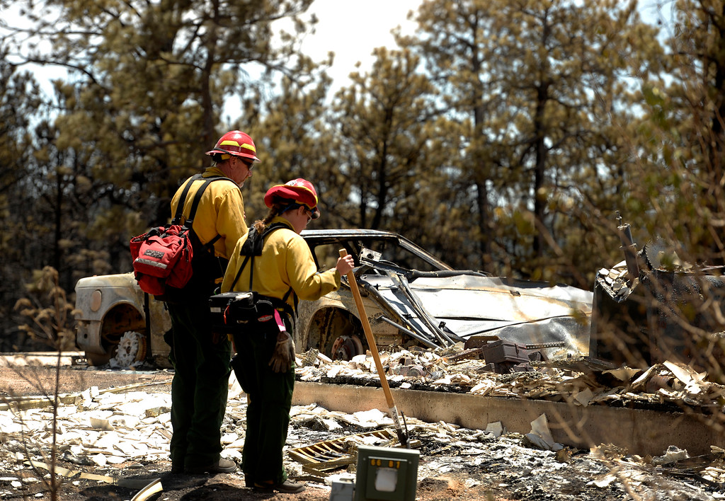 . BLACK FOREST, CO - JUNE 17:   Salida Fire Department engine boss and captain David McCann, left, and firefighter Brandie Smith, look over burned homes in the Black Forest Fire sone on June 17, 2013.  The crew were checking for hotspots as well as marking  trees that they deem dangerous that might fall over  on burned properties.  They mark them and sawyers can come in later to cut them down.  The crew also looks above in the burned canopy of trees looking for any limbs or trees that might fall over that might injure someone.  The fire is now 75% contained and recent rains are helping firefighters. Photo by Helen H. Richardson/The Denver Post)
