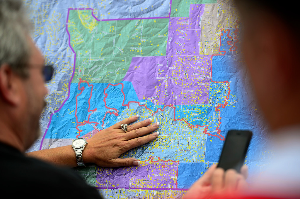 . COLORADO SPRINGS, CO - JUNE 18: Residents look at a map as Sheriff Terry Maketa explains it to them during a press conference held by the El Paso County Sheriff to inform residents of their re-admittance status. Residents in Cathedral Pines were allowed in by 2 p.m., while residents between Vollmer and Herring Roads and Black Forest and Herring Roads both locations between Shoup Road and Kirk Road north-south will be allowed in for three hours. (Photo by AAron Ontiveroz/The Denver Post)