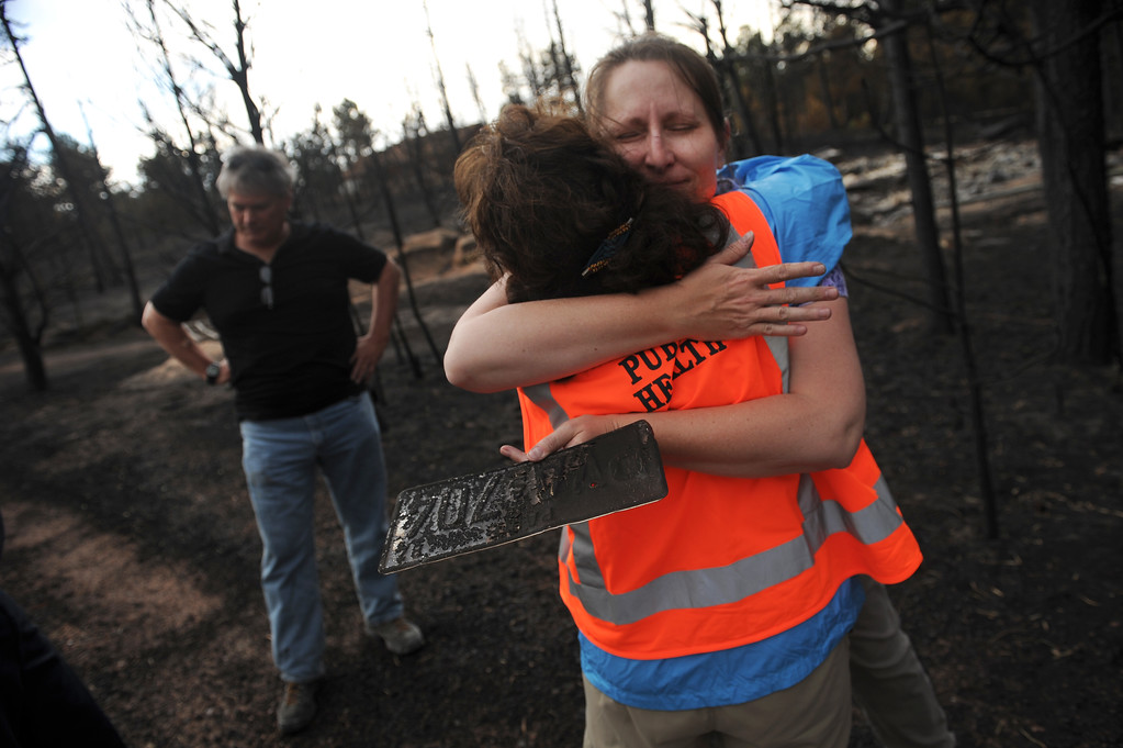 . BLACK FOREST, CO - JUNE 17:  Homeowner Amy Feik, right, gets a hug from Monika Hannan, a public health psychologist with El Paso County on June 18, 2013 on the property she lived on with boyfriend Robert Runyard, left.  The couple returned home for the first time to their home on Swan Road in Black Forest, CO on June 17, 2013.  Residents of Black Forest were finally allowed back into their burned homes for the first time since the fire devoured thousands of acres inside the Black Forest taking with it 502 homes and two lives.  Photo by Helen H. Richardson/The Denver Post)