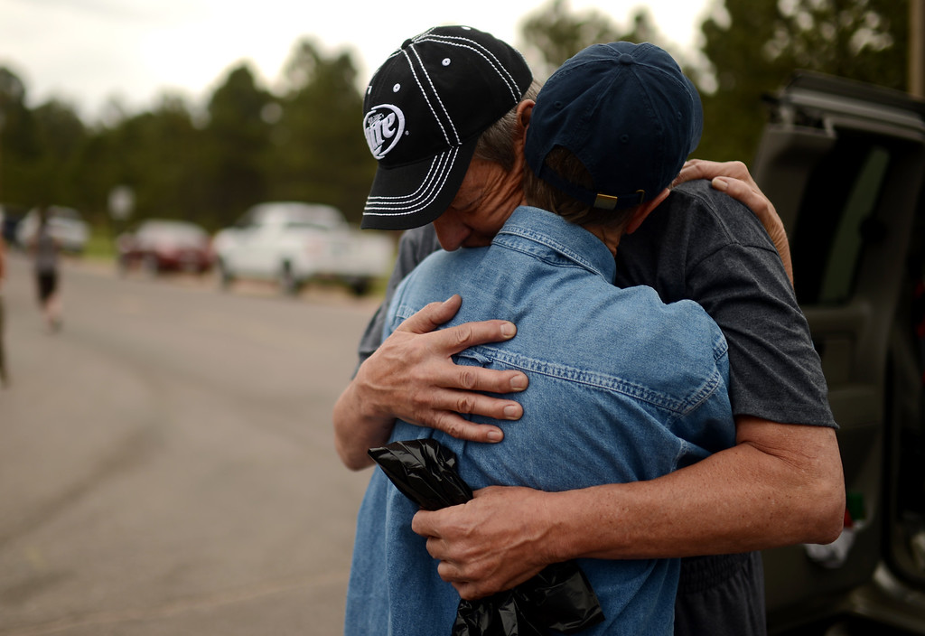 . Black Forest Fire evacuees Cindy Miller, hugs her husband Ray before his going to their property with El Paso County Sheriff\'s escort at the corner of Vollmer Rd. and Burgess Rd, June 14, 2013. Ray went to pick up their truck. They lost their house by the fire. (Photo By Hyoung Chang/The Denver Post)