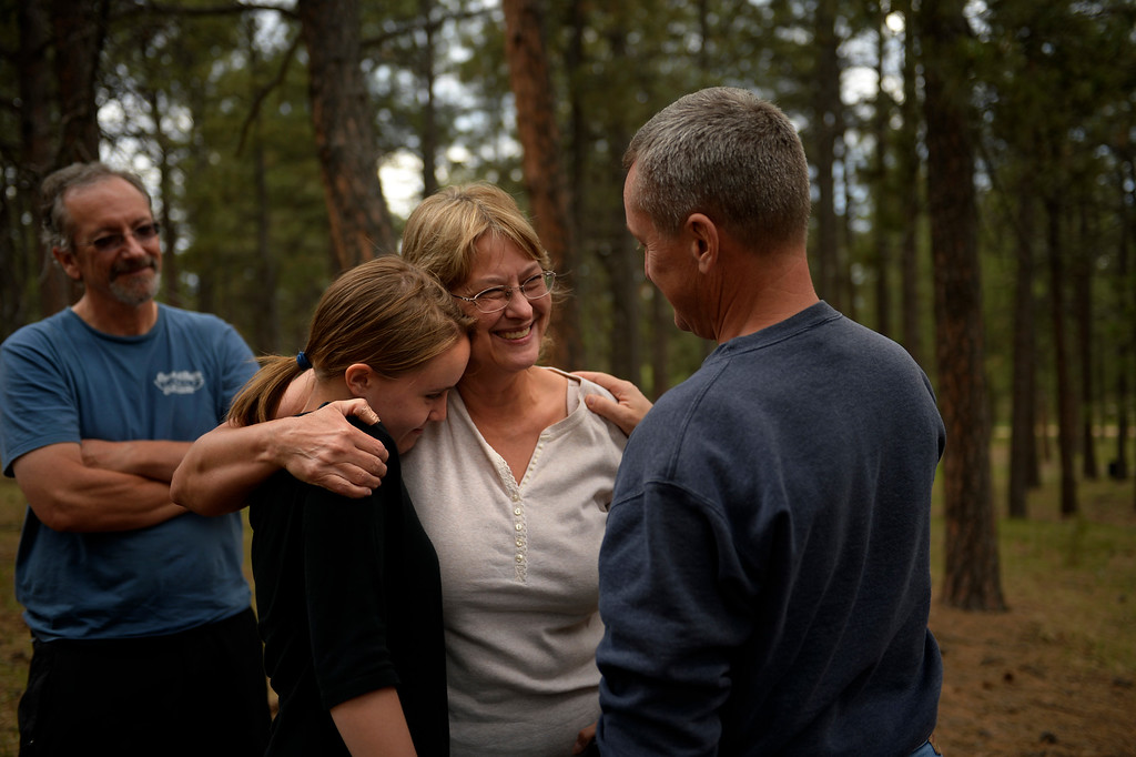 . COLORADO SPRINGS, CO. - June 17: Nancy Trosper is hugged by 18 year old Lauren Haynes and her dad Hank while Paul Story watches from behind. The neighbors were thankful their houses were still standing as they walked with Nancy through her property this afternoon in Willow Springs Estates. Some residents were allowed back into the northern edge of the Black Forest Fire area near Colorado Springs, Colorado. June 17, 2013 Denver, Colorado Springs. (Photo By Joe Amon/The Denver Post)