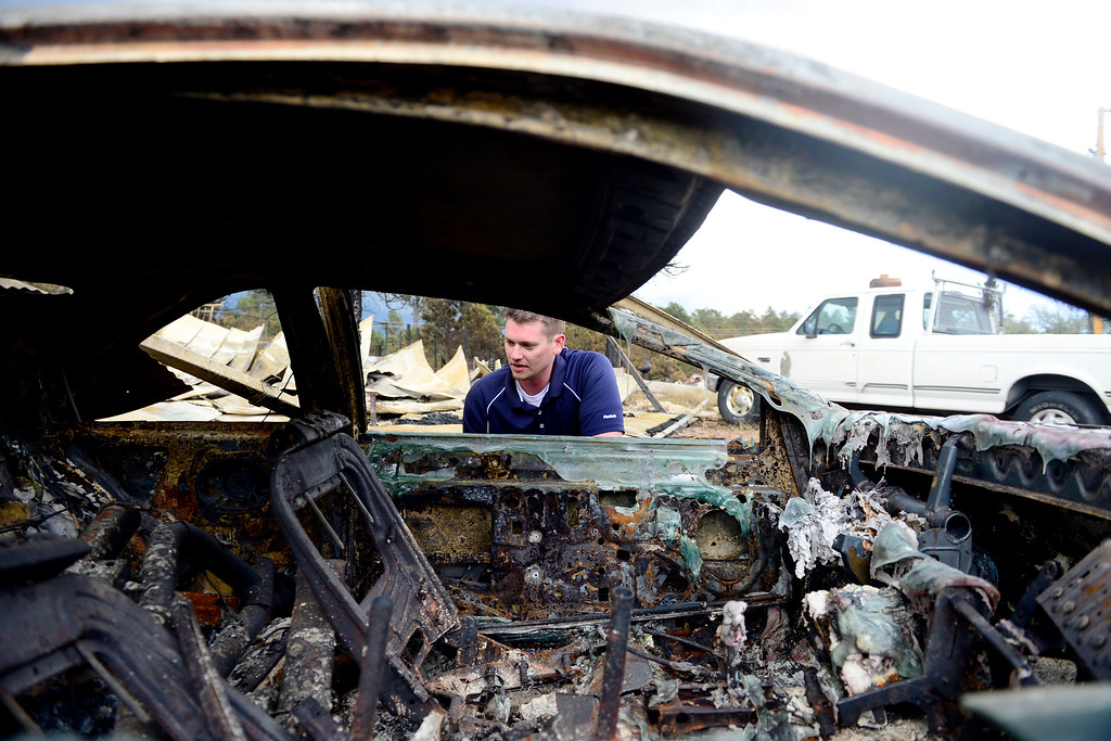 . COLORADO SPRINGS, CO - JUNE 18: Jesse Russow surveys the damage of a Ford T-Bird on his rental property, which was the southernmost home burned on the west side of Vollmer Road. The occupant of the home, who was not named, was only able to save himself and his motorcycle as he was away from the property when the evacuation took place. Russow is accepting donations for fire crews at 7195 Templeton Gap Road in Colorado Springs. (Photo by AAron Ontiveroz/The Denver Post)