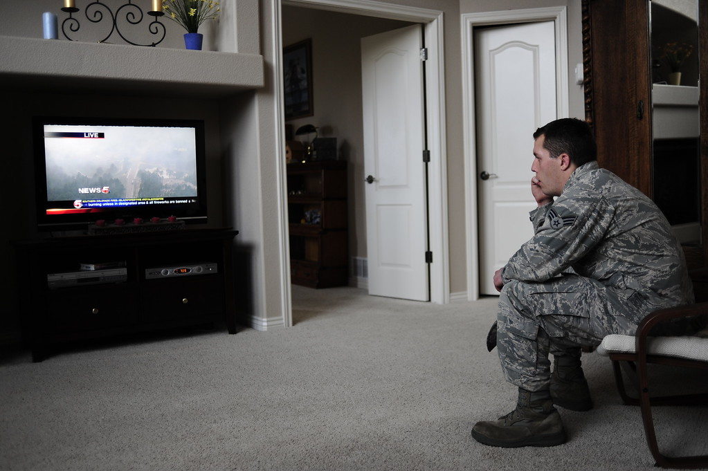 . COLORADO SPRINGS - JUNE 13: Jared Scott watches the news for updates on the Black Forest fire in his soon-to-be parent-in-laws\' home while helping them evacuate on June 13, 2013. Photo By Grant Hindsley / The Denver Post)