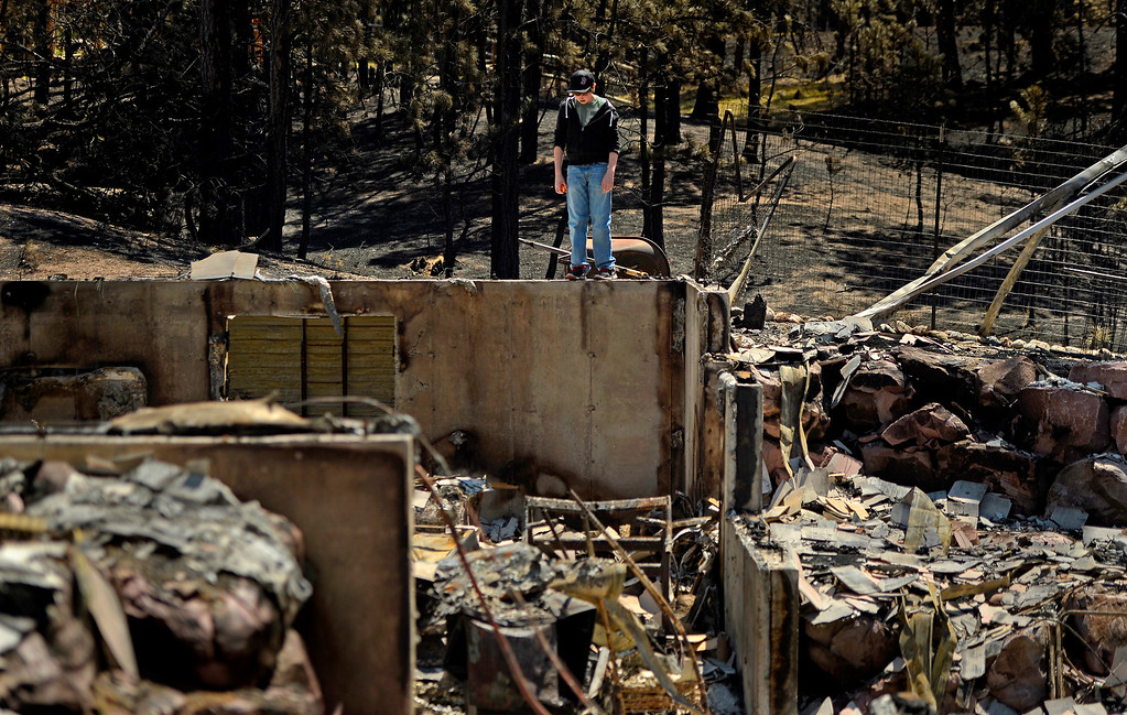 . Nolan Schultz, 16, stands amid the ruins of his destroyed home on June 19, 2013. After being evacuated for about a week, his family was allowed to return to the area to view the damage.