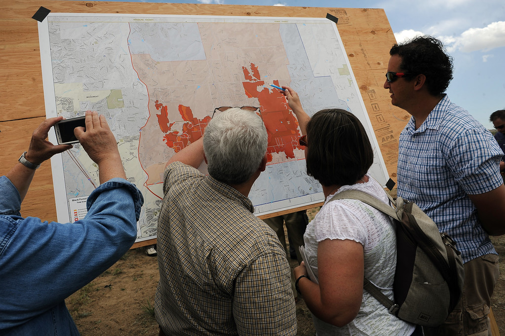 . Black Forest evacuees look at a map of the perimeter of the Black Forest Fire after a press briefing about the Black Forest Fire held for members of the media and for homeowners at Pikes Peak Community College Rampart Range Campus near Monument, CO  on June 15, 2013.  Photo by Helen H. Richardson/The Denver Post)