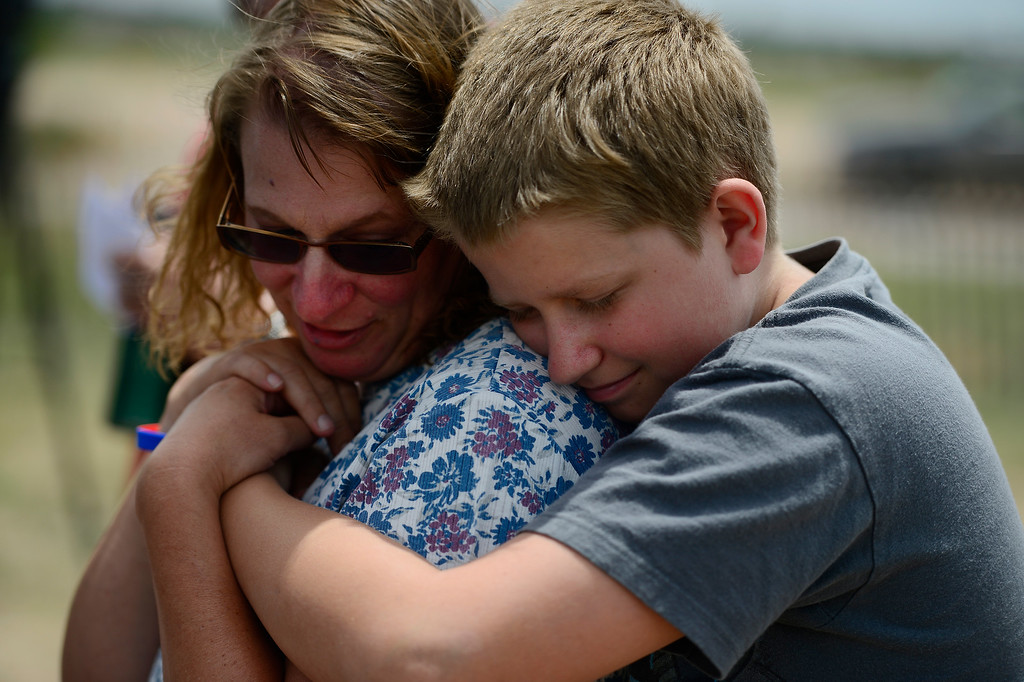 . COLORADO SPRINGS, CO - JUNE 18: Kim Redus is hugged by her son Zach, 12, as they listen during a press conference held by the El Paso County Sheriff to inform residents of their re-admittance status. Residents in Cathedral Pines were allowed in by 2 p.m., while residents between Vollmer and Herring Roads and Black Forest and Herring Roads both locations between Shoup Road and Kirk Road north-south will be allowed in for three hours. (Photo by AAron Ontiveroz/The Denver Post)