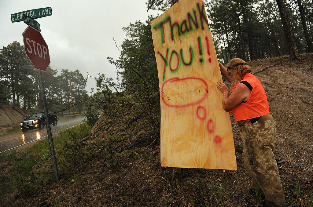 . BLACK FOREST, CO - JUNE 17:   Amidst a downpour of rain and hail, Black Forest resident Mike Turner puts out a sign saying Thank You to all the firefighters whom he called absolute heroes along Shoup Road in Black Forest, CO on June 17, 2013.  Turner never evacuated from the fire and tried to save his mother\'s house and property.  His mother, who is 90 years old, has lived in the Black Forest for 49 years.  She lost everything in the fire.    Photo by Helen H. Richardson/The Denver Post)