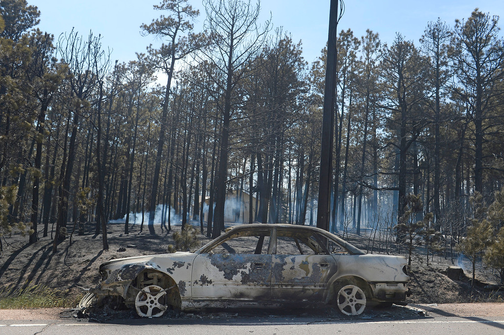 . COLORADO SPRINGS, CO - JUNE 12: A car parked along Black Forest Road is destroyed by the Black Forest Fire on June 12, 2013.  The Black Forest Fire continues to burn and high winds are expected throughout the rest of the day.  Photo by Helen H. Richardson/The Denver Post)