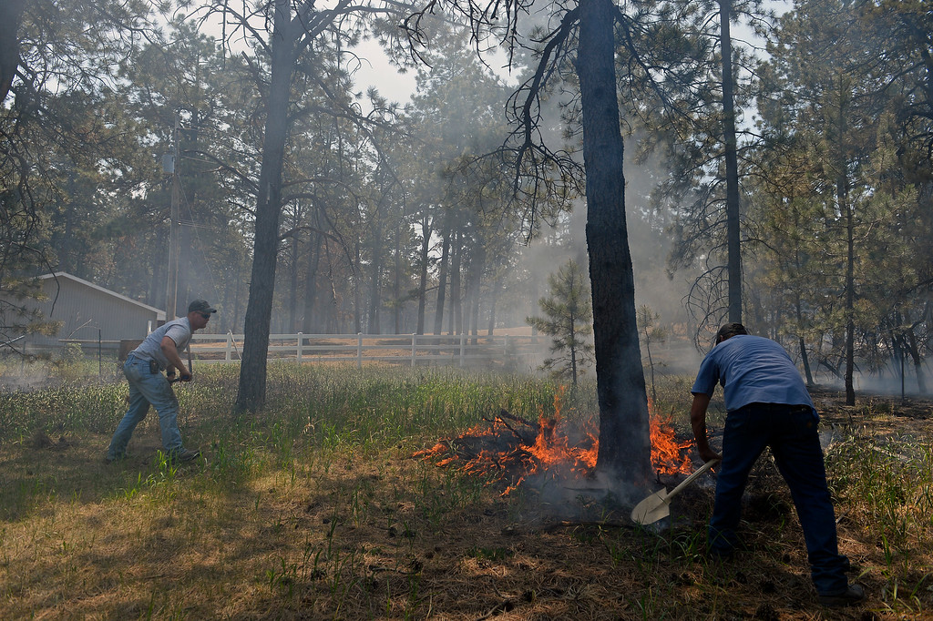 . COLORADO SPRINGS, CO - JUNE 12:  Matt Newland, left, and friend Chad Mazari take shovels in around neighbors houses to help put out small fires off of Cyprus road in the Black Forest on June 12, 2013. He and his friend Matt Newland stayed close to their house on Herring Road to make sure they could watch the fire to protect their house.  They had all of their belongings ready to go and an escape route in place in case they need to leave. So far the fire has moved east of their house, but the Black Forest fire continues to burn and has yet to have any containment.   Photo by Helen H. Richardson/The Denver Post)