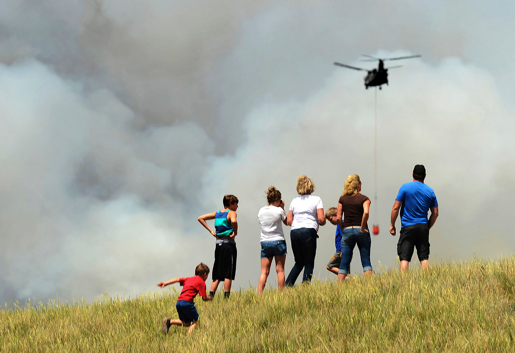 . People climb a hill to watch helicopters gather water to dump on the Black Forest fire on June 12, 2013. According to El Paso County Sheriff Terry Maketa, the Black Forest fire, north of Colorado Springs, had already burned 80-100 homes.