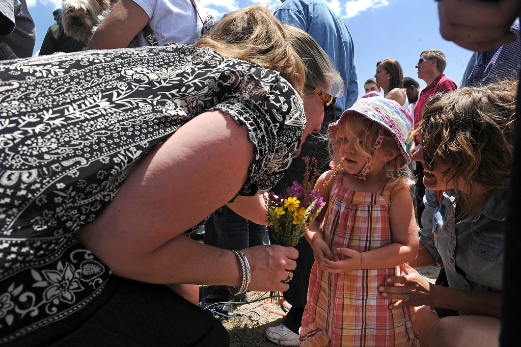 . 2 year old  Saylor Brown gives flowers to Black Forest fire evacuee Cheryl Carden, during a press briefing about the Black Forest Fire held for members of the media and for homeowners at Pikes Peak Community College Rampart Range Campus near Monument, CO  on June 15, 2013. Carden knows that she lost her home in the fire. Brown\'s aunt Rebecca Abernathy is at right.  Photo by Helen H. Richardson/The Denver Post)