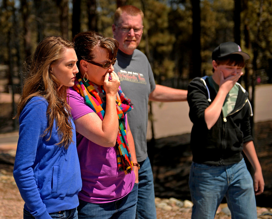 . The Schultz family - from left, Annissa, 20, mother Camla, father Mike and brother Nolan, 16 - look at their destroyed home for the first time as residents were allowed to return to the Black Forest fire burn zone on June 19, 2013. The family had lived in the house for eight years. The family\'s home was one of 509 houses destroyed in the fire.