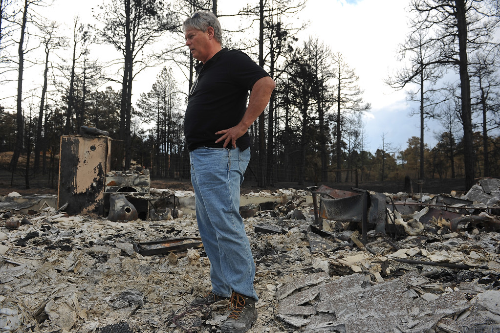 . BLACK FOREST, CO - JUNE 18:  Robert Runyard surveys what is left of his home on Swan Road in Black Forest, CO on June 18, 2013.  Runyard and his girlfriend Amy Feik, not pictured, returned home for the first time to their home on Swan Road in Black Forest, CO on June 17, 2013.  Residents of Black Forest were finally allowed back into their burned homes for the first time since the fire devoured thousands of acres inside the Black Forest taking with it 502 homes and two lives.  Photo by Helen H. Richardson/The Denver Post)