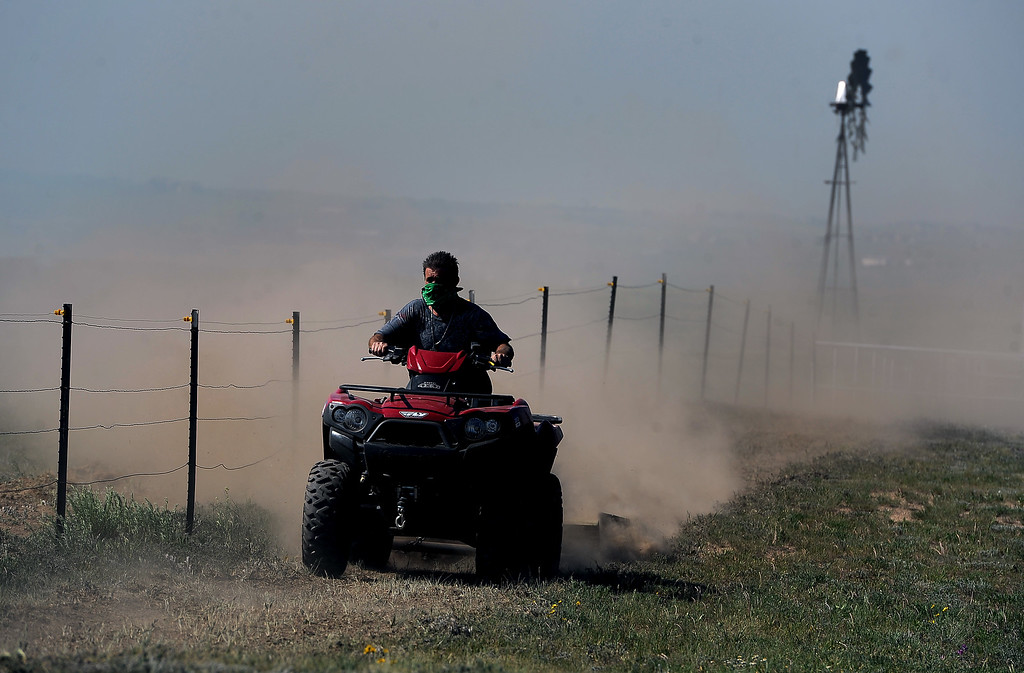 . COLORADO SPRINGS, CO - JUNE 12: Using an ATV with a grader on the back a homeowner work aggressively to create a fire line around his ranch just off of Black Forest Road to save it from the Black Forest Fire in the Black Forest on June 12, 2013.   Photo by Helen H. Richardson/The Denver Post)