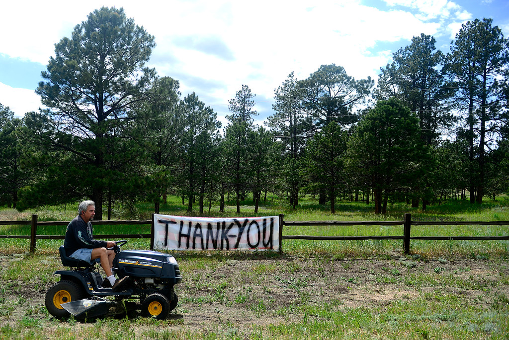 . COLORADO SPRINGS, CO - JUNE 17: Kevin Kline, a resident of Highway 83 south of Hodgen Road, mows his grass as a precautionary measure to protect his home in the event that another fire hits the area. Kline, along with his wife and 10 dogs, was among those evacuated last week as the Black Forest Fire grew. (Photo by AAron Ontiveroz/The Denver Post)