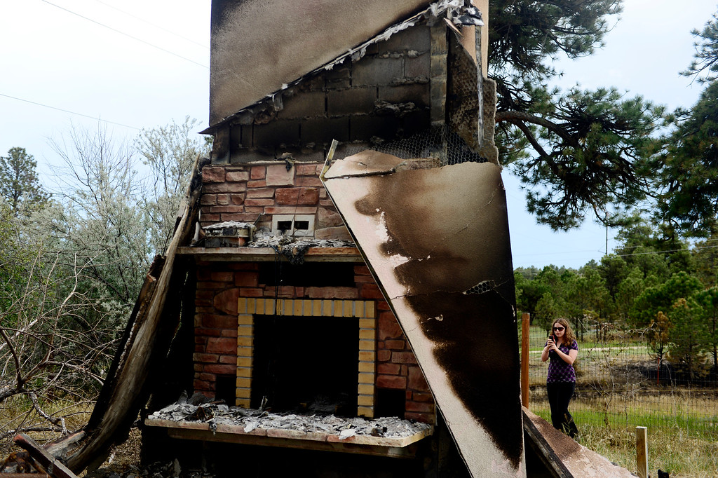. COLORADO SPRINGS, CO - JUNE 18: Audrea Branham photographs a chimney at a rental property owned by Jesse Russow, which was the southernmost home burned on the west side of Vollmer Road. The occupant of the home, who was not named, was only able to save himself and his motorcycle as he was away from the property when the evacuation took place. Russow is accepting donations for fire crews at 7195 Templeton Gap Road in Colorado Springs. (Photo by AAron Ontiveroz/The Denver Post)