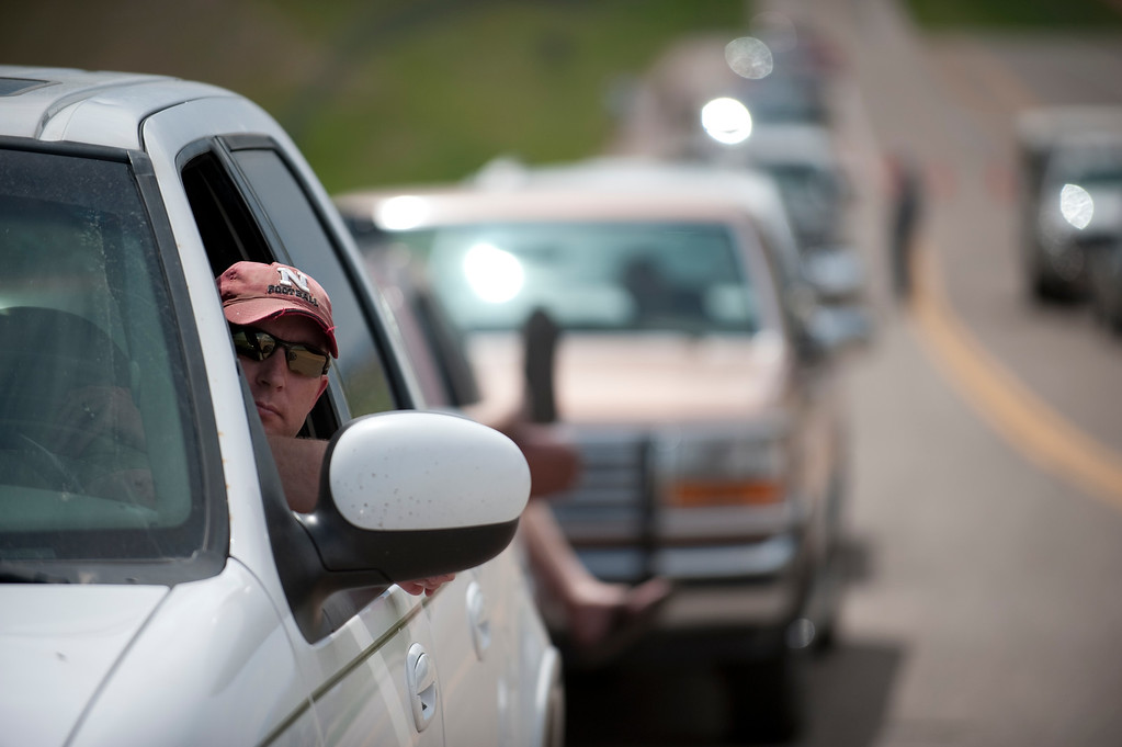 . Ty Ruter waits in line at Highway 83 and Hodgen Road to be escorted to his home in Black Forest by police on Saturday, June 15, 2013. (Photo By Grant Hindsley / The Denver Post)