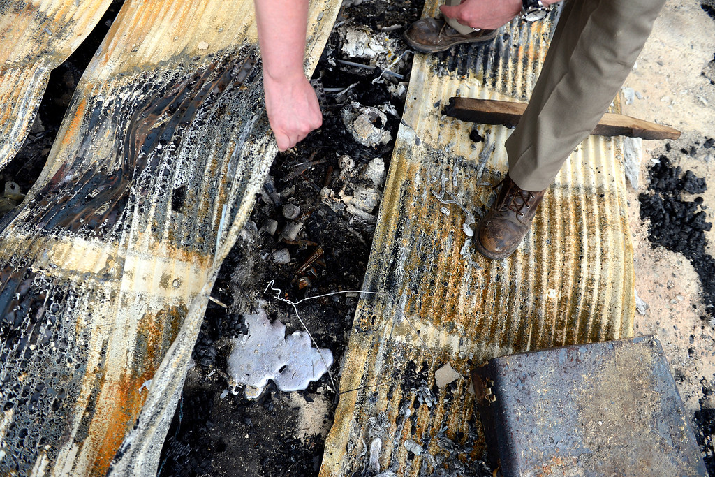 . COLORADO SPRINGS, CO - JUNE 18: Jesse Russow looks at a puddle of aluminum that was formerly a set of rims as he surveys the damage of his rental property, which was the southernmost home burned on the west side of Vollmer Road. The occupant of the home, who was not named, was only able to save himself and his motorcycle as he was away from the property when the evacuation took place. Russow is accepting donations for fire crews at 7195 Templeton Gap Road in Colorado Springs. (Photo by AAron Ontiveroz/The Denver Post)