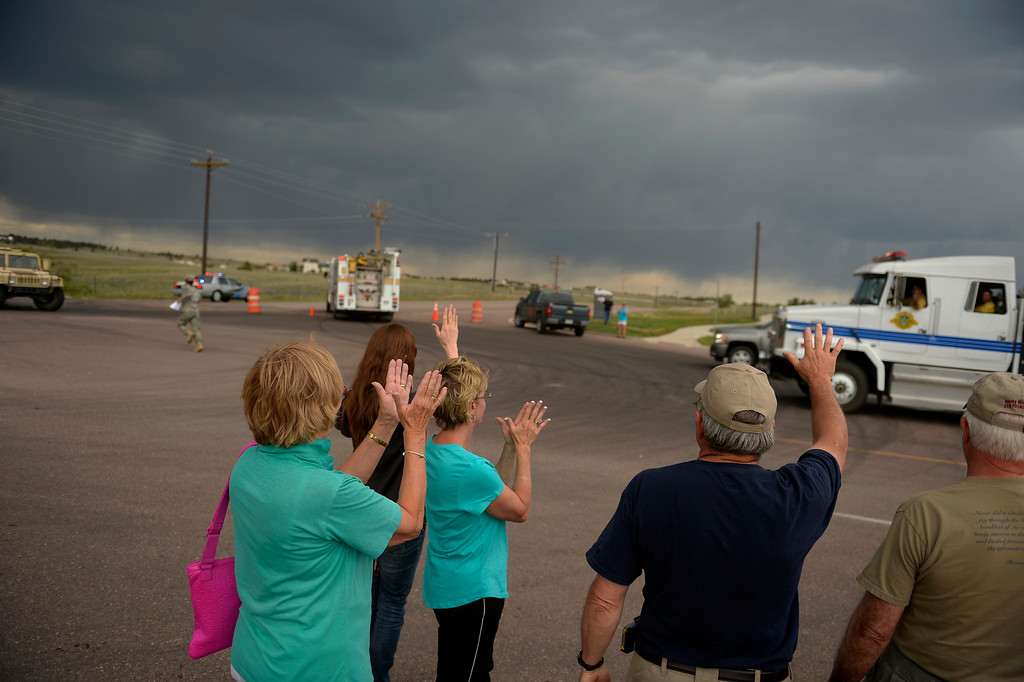 . COLORADO SPRINGS, CO. - June 14: Residents wave and clap at passing firefighters as they wait for their escourt into the Black Forest Fire area to quickly get medications and important items that were left behind in the rush to evacuate near Colorado Springs, Colorado. June 14, 2013 Denver, Colorado Springs. (Photo By Joe Amon/The Denver Post)