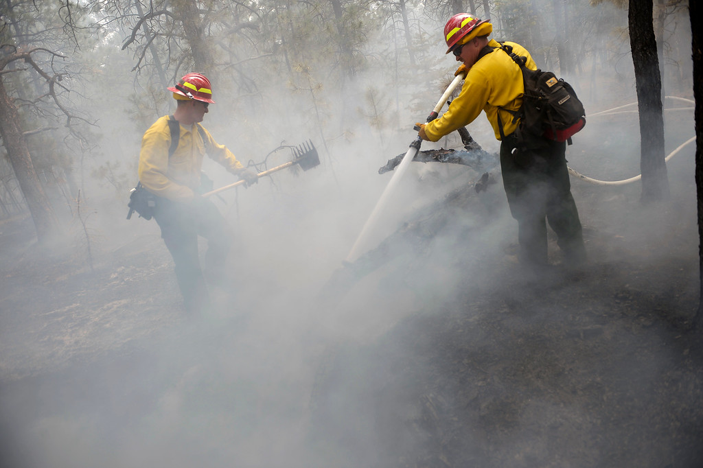 . 1st Sgt John Screiber, left, helps put out fire while Sgt David Meggison, right puts water on hotspots  on property along Winchester Road north of Hodgen Road in the midst of the Black Forest Fire on June 13, 2013.  Photo by Helen H. Richardson/The Denver Post)