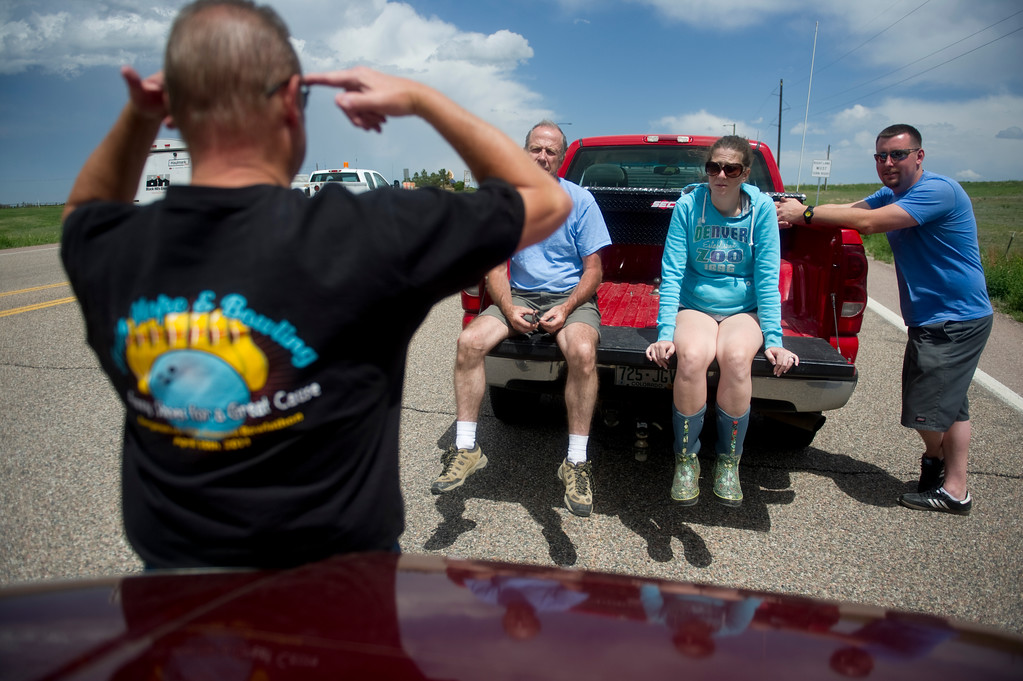 . Mike Perry, left, tells a story from his days in the military to John Adamson, his daughter, Heather Stanley, and her husband Shawn Stanley, while waiting in line to be escorted to their respective homes in Black Forest on Saturday, June 15, 2013. Police were only letting residents in, with proof of residence, for pets or medications.  (Photo By Grant Hindsley / The Denver Post)