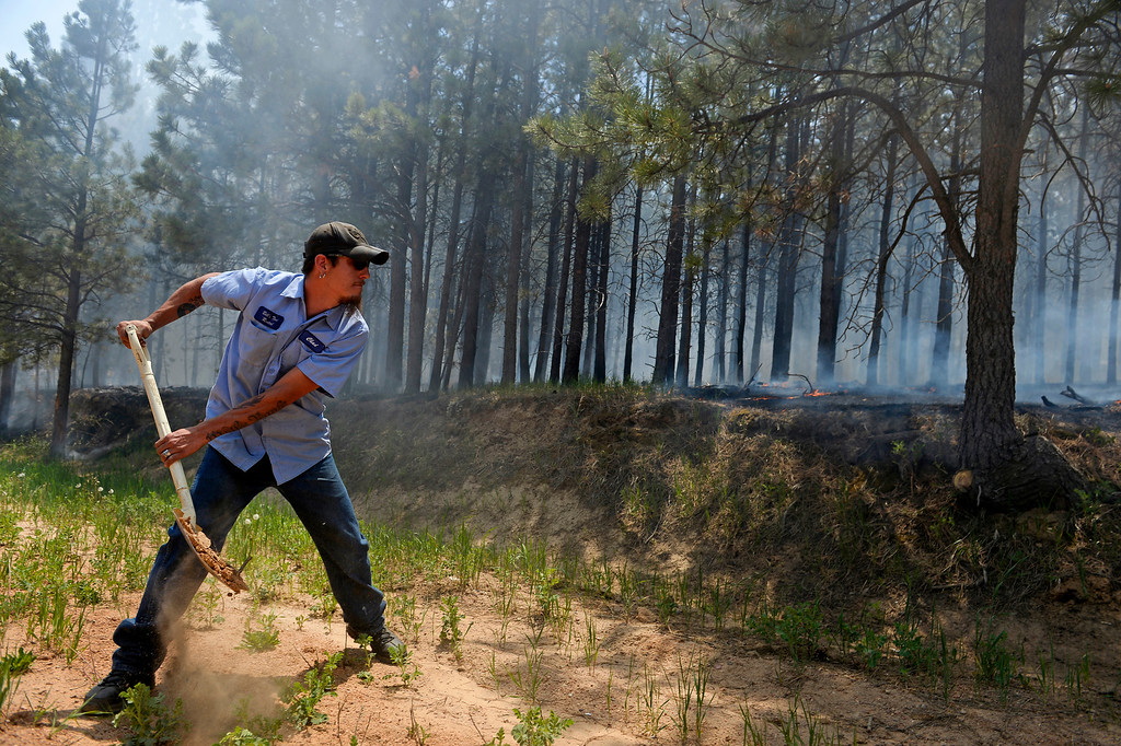 . COLORADO SPRINGS, CO - JUNE 12:  Chad Mazari helps to put dirt on active fire around neighbors houses off of Cyprus road in the Black Forest on June 12, 2013. He and his friend Matt Newland stayed close to their house on Herring Road to make sure they could watch the fire to protect their house.  They had all of their belongings ready to go and an escape route in place in case they need to leave. So far the fire has moved east of their house, but the Black Forest fire continues to burn and has yet to have any containment.   Photo by Helen H. Richardson/The Denver Post)