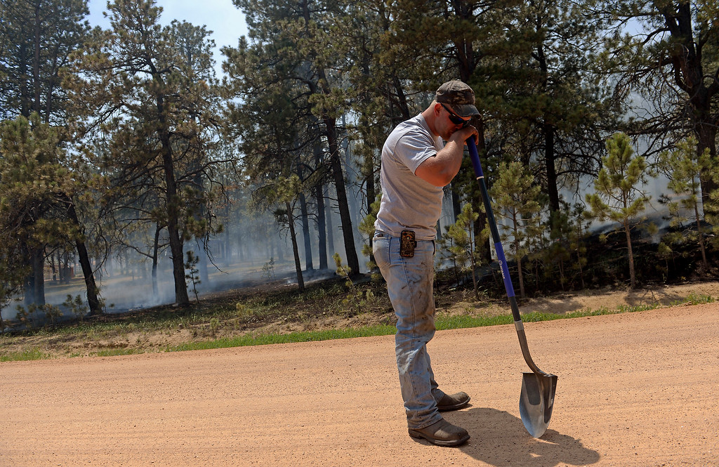 . COLORADO SPRINGS, CO - JUNE 12:  Matt Newland takes a break from helping put out small fires with friend Chad Mazari around neighbors houses off of Cyprus road in the Black Forest on June 12, 2013. He and his friend Matt Newland stayed close to their house on Herring Road to make sure they could watch the fire to protect their house.  They had all of their belongings ready to go and an escape route in place in case they need to leave. So far the fire has moved east of their house, but the Black Forest fire continues to burn and has yet to have any containment.   Photo by Helen H. Richardson/The Denver Post)