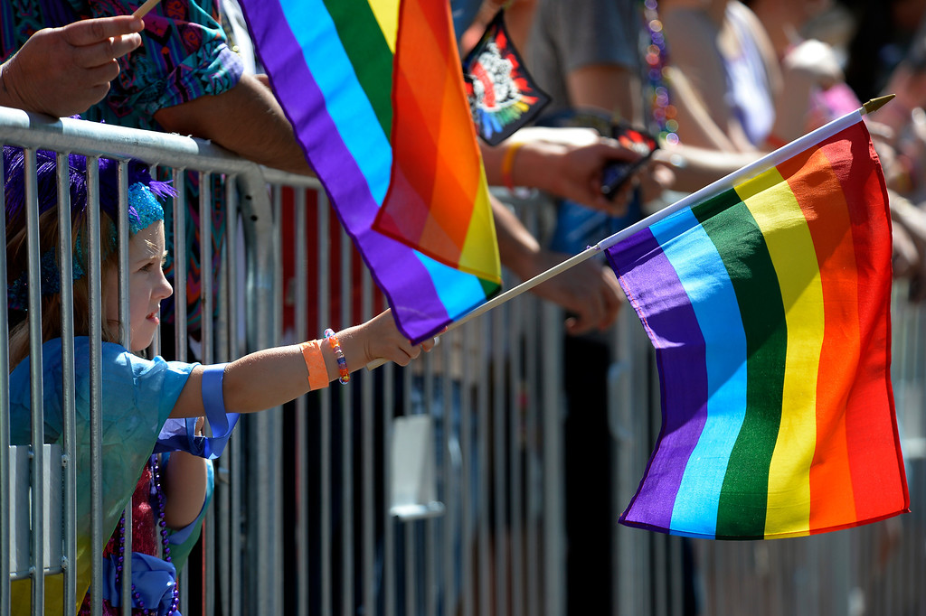 . DENVER, CO. - JUNE 16: Violet Biegert 4 1/2 waves her flag during the Pridefest Parade in downtown Denver June 16, 2013. The color guard this year will include gay vets and active service men and women -- wouldn\'t have happened five years ago. (Photo By John Leyba/The Denver Post)