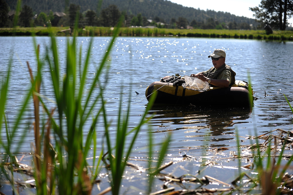 . EVERGREEN, CO - JUNE 21: George Pollack floats in the middle of Buchanan Pond while fly fishing in Evergreen, Colorado on June 21, 2013. Members of the Evergreen Trout Unlimited are allowed a day of free fishing at the pond for their volunteer service teaching children how to fish. (Photo by Seth McConnell/The Denver Post)
