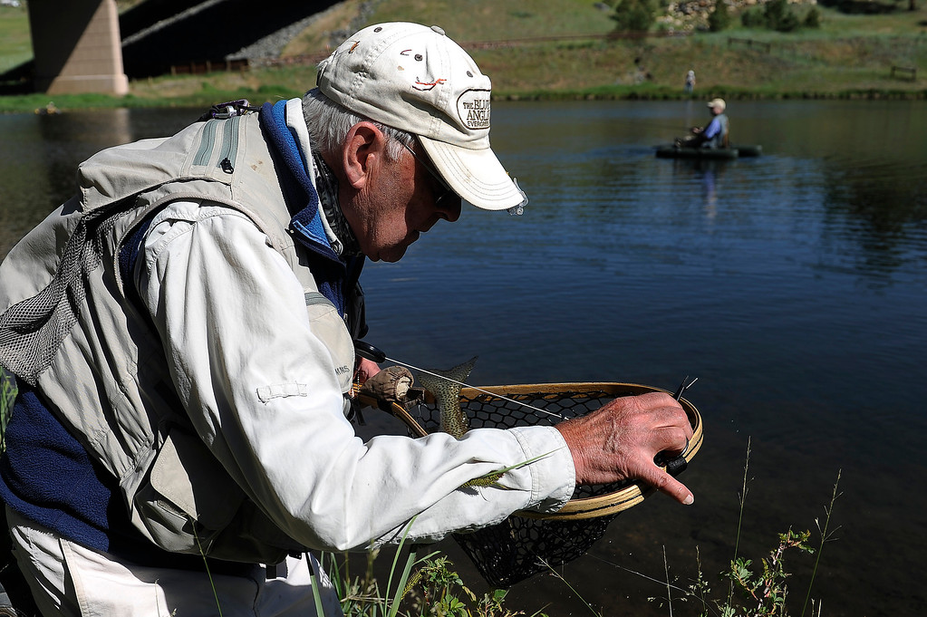 . EVERGREEN, CO - JUNE 21: Ford Oliphant removes the hook from a fish he caught at Buchanan Pond in Evergreen, Colorado on June 21, 2013. Members of the Evergreen Trout Unlimited are allowed a day of free fishing at the pond for their volunteer service teaching children how to fish. (Photo by Seth McConnell/The Denver Post)