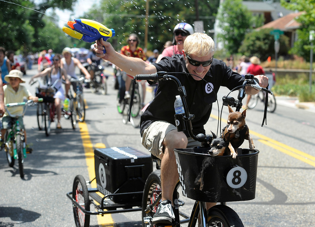 . DENVER, CO - JULY 4: Tim Schaefer and his companions Maximus, left, and Lucille, get in to a water fight with the crowd as the fourth annual Park Hill 4th of July Parade winds its way down 23rd Avenue complete with marching bands, neighborhood sponsored floats, bikes and classic cars. (Photo By Kathryn Scott Osler/The Denver Post)