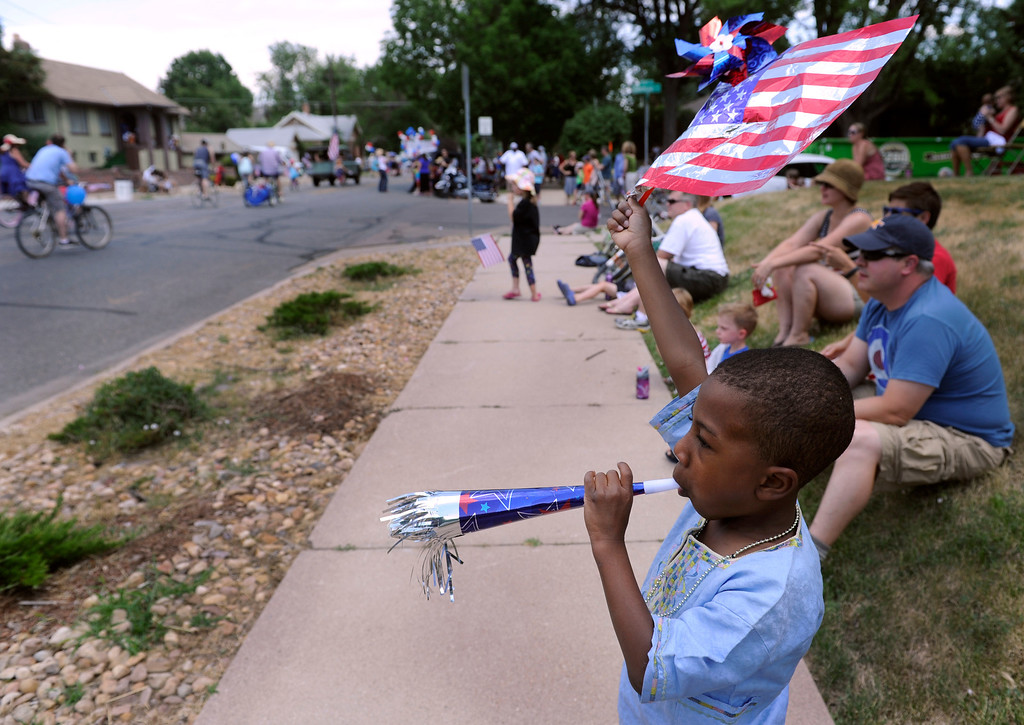 . DENVER, CO - JULY 4: Menkhu Jones, 6, toots his horn and waves his flag as the fourth annual Park Hill 4th of July Parade winds its way down 23rd Avenue complete with marching bands, neighborhood sponsored floats, bikes and classic cars. (Photo By Kathryn Scott Osler/The Denver Post)