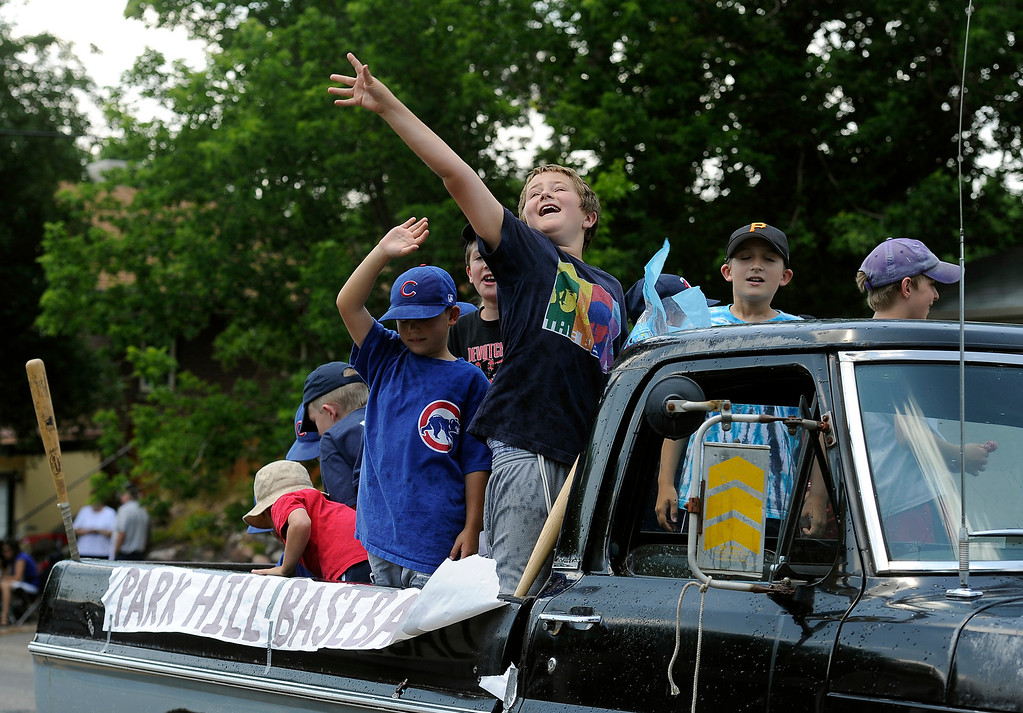 . DENVER, CO - JULY 4: The Park Hill baseball team toss candy to the crowd gathered to watch the fourth annual Park Hill 4th of July Parade winds its way down 23rd Avenue complete with marching bands, neighborhood sponsored floats, bikes and classic cars. (Photo By Kathryn Scott Osler/The Denver Post)