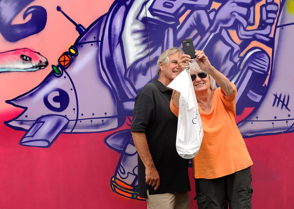 . DENVER, CO. - JULY 5:  Paul and Catherine Kuerbis posed for a picture in front of a colorful mural on St. Paul Street as they walked through the Cherry Creek Arts Festival Friday. They wanted to send a photograph of themselves to their grandchildren in Syracuse, New York. Cherry Creek Arts Festival opened for the weekend Friday afternoon, July 5, 2013, featuring 250 artists displaying their work. The annual event runs through the weekend. Photo By Karl Gehring/The Denver Post
