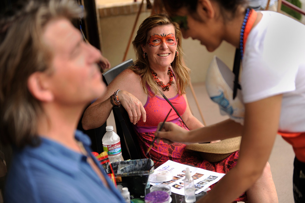 . DENVER, CO. - JULY 5:  Debbie Young, center, watched as artist Diana Ariana, right, prepared to paint the face of Young\'s husband Gary Stevens, left, at the Cherry Creek Arts Festival Friday. Ariana works at La Piccola Venezia, a new cafe on Steele Street. Cherry Creek Arts Festival opened for the weekend Friday afternoon, July 5, 2013, featuring 250 artists displaying their work. The annual event runs through the weekend. Photo By Karl Gehring/The Denver Post
