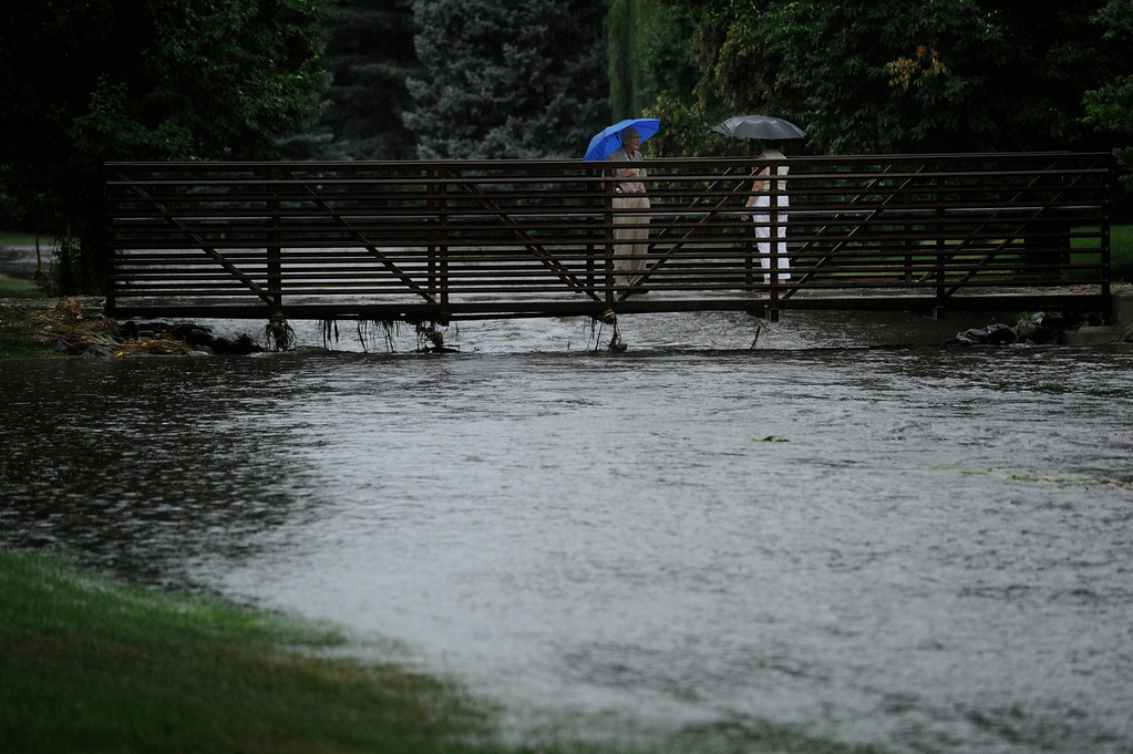 . DENVER, CO - JULY 13:  Folks stand on a pedestrian bridge over a swollen  gulch at McWilliams Park near Yale Ave and Fillmore St. in Denver Colorado, July 13, 2013 after a heavy rainstorm. (Photo By Andy Cross/The Denver Post)